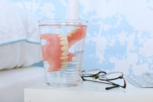 soaking dentures on bedside table