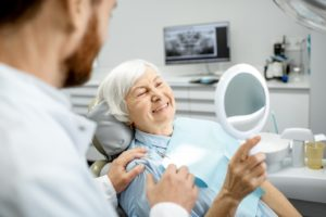 Patient admiring smile after transitioning from dentures to dental implants